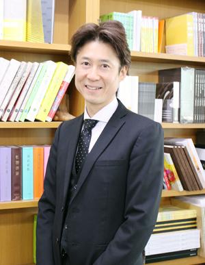 クータ・バインディングで製本された書籍の前で渋谷社長