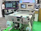 ナビタスビジョン、小型横軸ロールラベル検査装置を発表